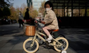 A girl wearing a protective face mask cycles along a business street on December 5, 2020 in Wuhan, Hubei province, China.