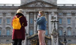 A woman wearing a mask outside Buckingham Palace in London.