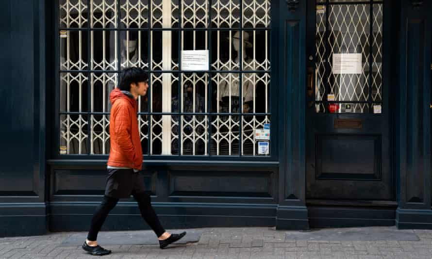 A walker passes closed shops in central London.