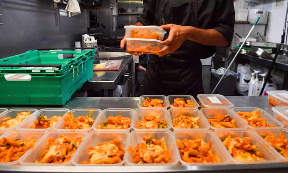 Kitchen staff at a pub preparing free packed lunches for children in December 2020.