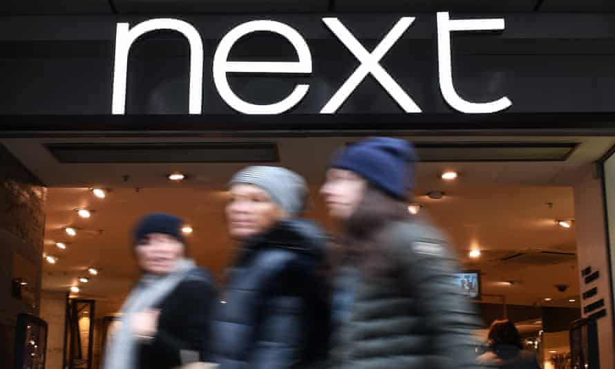 Shoppers pass a Next clothing store
