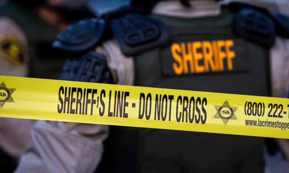 Los Angeles sheriff's deputies stand behind police tape.