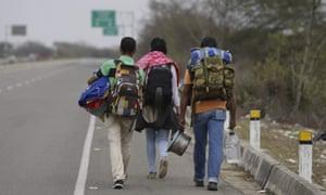 Venezuelan Omar Mujica, right, walks to Lima along the shoulder of the Pan-American Highway.