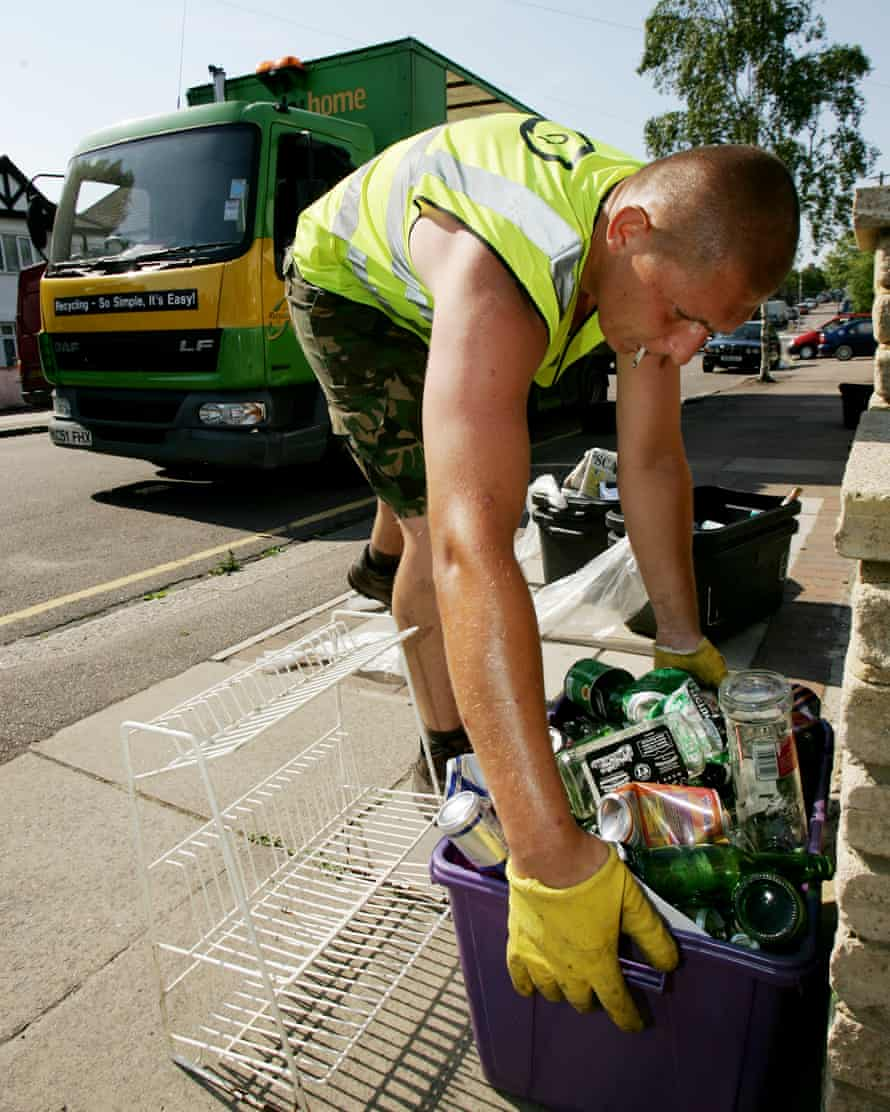 A member of the recycling team in Barnet, London, collects a box of cans and bottles