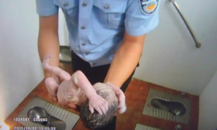 Handout image shows a frame grab of a Beijing Tianqiao Police video taken on August 2, 2015 that shows a Chinese policeman holding an abandoned newborn baby in a public toilet in Beijing.