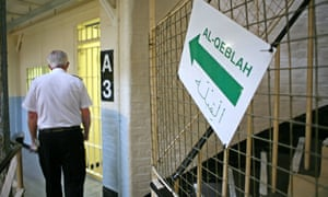 A guard walks past a sign to the mosque inside Wandsworth prison.