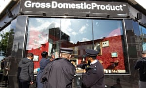 Police officers and members of the public gather outside Gross Domestic Product, a homewares store being launched in south London by Banksy