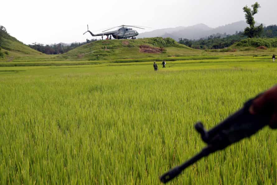 A Myanmar army helicopter transports journalists to an area where government forces found the bodies of Hindu villagers, whom the authorities claim were killed by insurgents last month
