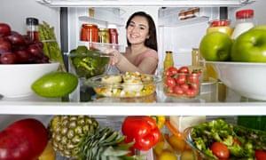 A woman opening a fridge door