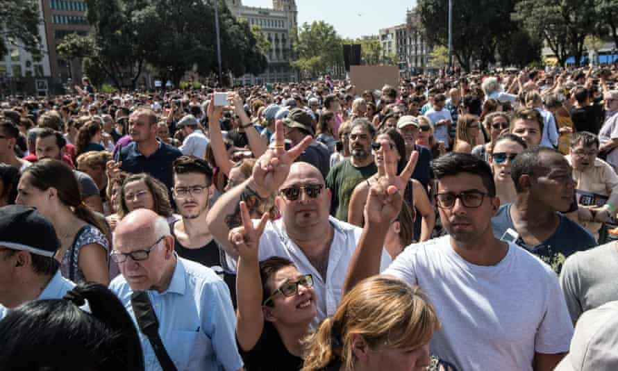 People gesture as they leave Plaça de Catalunya after the vigil