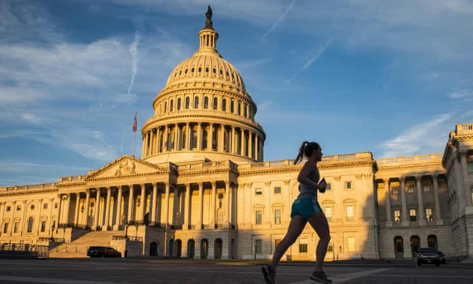 The rising sun illuminates the US Capitol Building in Washington.