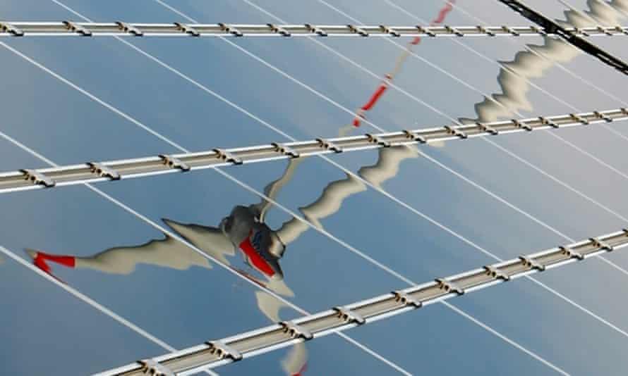 Wind turbine reflected in solar panel
