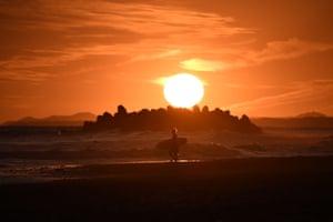 Hamamatsu, Japan: A surfer walks on the beach at sunset at Nakatajima-Sakyu Dunes