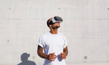 Man wearing Virtual Reality Glasses Young man over a concrete wall using a virtual reality headset