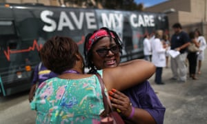 Margalie Williams, a cancer survivor, is hugged after speaking during a rally near Jackson Memorial hospital in Miami, Florida, as part of the Save My Care bus tour.