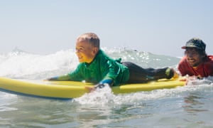 A youngster takes to the waves with one of the Wave Project's instructors.