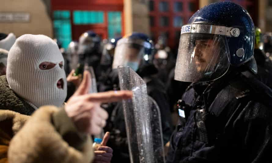 A protestor wearing a white balaclava points towards a police officer in riot gear on March 26, 2021 in Bristol