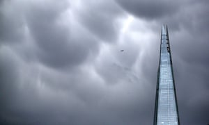 An aeroplane passes rain clouds above The Shard skyscraper on January 7, 2014 in London, England.