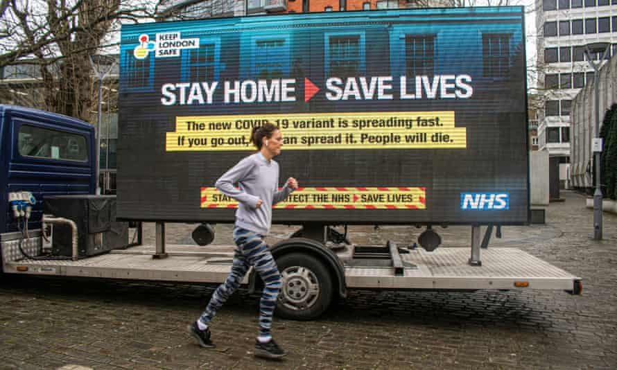 A jogger in London runs past an NHS Covid sign on Thursday