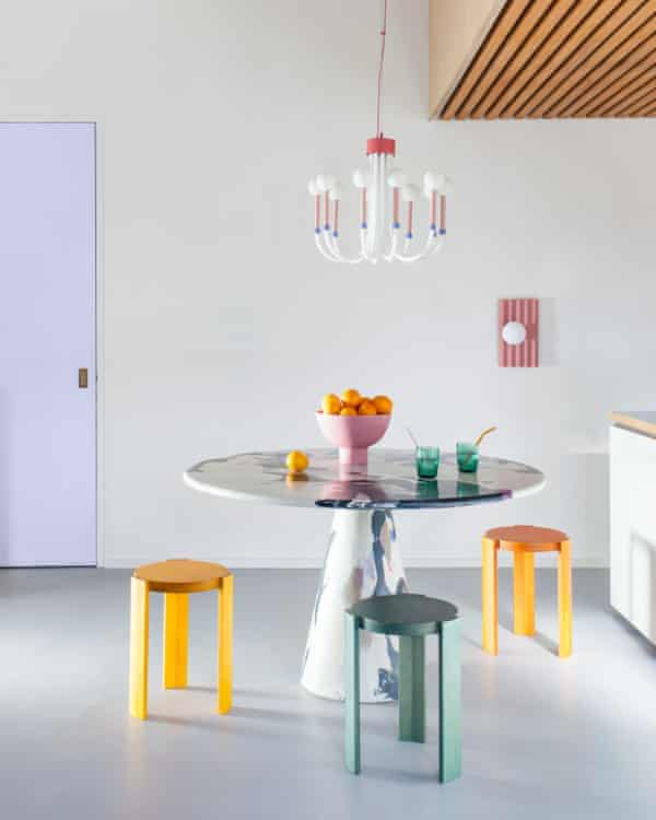 houseof lighting hanging over a table with bright-coloured stools