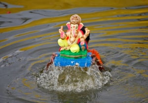 Ahmedabad: A boy immerses an idol of the Hindu god Ganesh into a pond on the second day of Ganesh Chaturthi festival