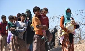 People walk through mine-filled areas to peshmerga-controlled areas in Kirkuk, Iraq.