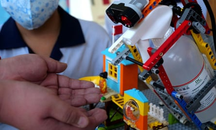 An elementary school student uses a self-built motion sensor controlled disinfectant dispenser assembled with Lego parts, following a novel coronavirus outbreak in the southern Taiwanese city of Kaohsiung