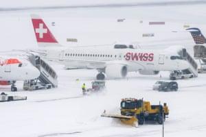 Snow ploughs clear runways at Geneva airport, Switzerland