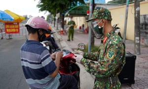 A Vietnamese soldier checks the travel documents of a motorist at a checkpoint in Ho Chi Minh City as the city enters lockdown.