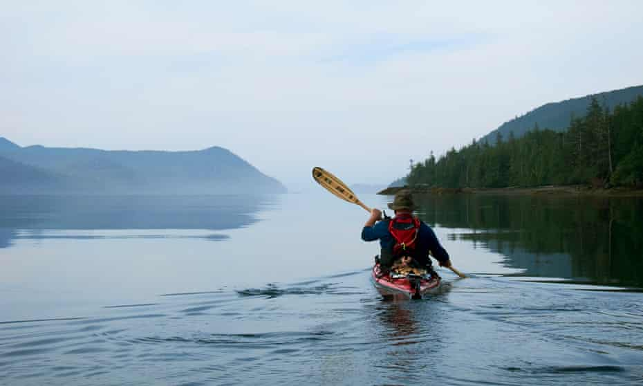 Guide Gord Pincock leads an early morning paddle on the calm waters in Gwaii Haanas, Haida Gwaii, Canada.