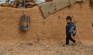 A small boy walks past the mud wall of a dwelling in Rukban settlement, near the Southern border of Syria.