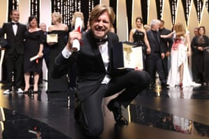 Swedish director Ruben Ostlund poses on stage with his trophy after he won the Palme d'Or for his film 'The Square' on May 28, 2017 during the closing ceremony of the 70th edition of the Cannes Film Festival in Cannes, southern France