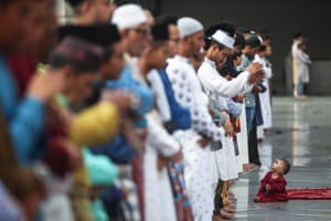 A girl looks up at men praying at the Federal Territory Mosque in Kuala Lumpur, Malaysia
