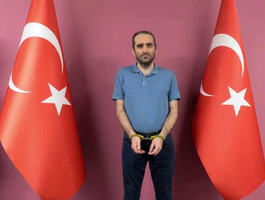 Selahaddin Gülen in handcuffs standing between two Turkish flags