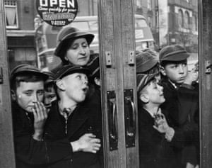 Let Us In, 1953. Children wait impatiently for a sweet shop to open.
