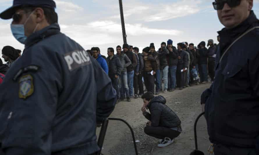 Men queue for registration documents at the Greek-Macedonia border at Idomeni.