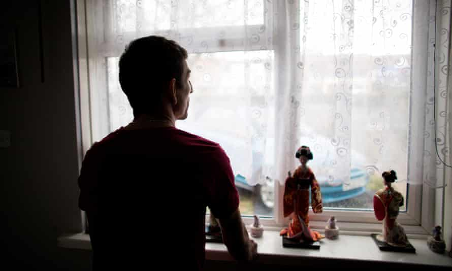 Man standing in his home looking out of a window