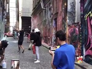 The group spraying over graffiti art in Melbourne's Hosier Lane.