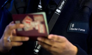 A border force officer examines a passport
