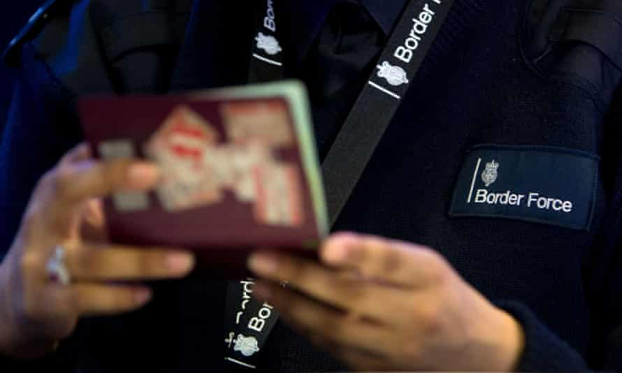 A Border Force officer checks a passport at Heathrow airport.