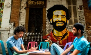 Fans relax at a Cairo cafe in front of a mural of Mo Salah, painted by Ahmed Fathy.