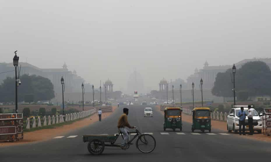 A cyclist paddles his cart as the city envelops in smog in New Delhi, India, in November 2019