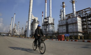 An oil worker rides his bicycle past Tehran's oil refinery