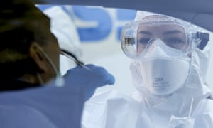 A medical worker wearing protective equipment and mask collects a mouth and nose swab from a person sitting inside a car during a drive-through coronavirus (Covid-19) test in Rome.