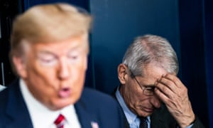 Fauci listens to Trump at a briefing on 20 March.