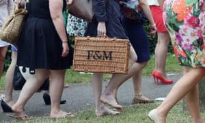 Women at Royal Ascot carry a Fortnum & Mason hamper