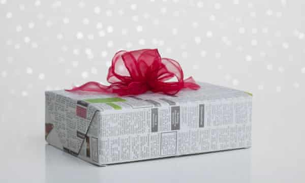 Studio shot of gift wrapped in newspaper on sparkled background