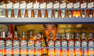 A bartender takes a bottle of Johnnie Walker whisky