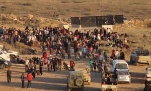 Syrians wait at the border areas near Jordan after they fled from the ongoing military operations
