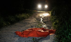 Covered-up body of a young man who was shot dead lies at a crime scene in San Pedro Sula